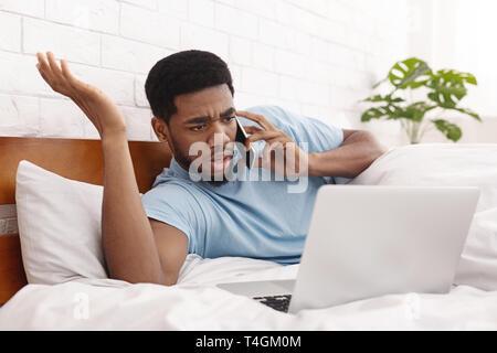 Homme en colère des problèmes avec l'ordinateur portable talking on mobile phone Banque D'Images