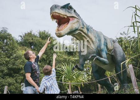 Heureux père et fils jouant dans l'aventure à dino park le jour. Les gens s'amuser à l'extérieur. Concept de vacances estivales et ambiance familiale.