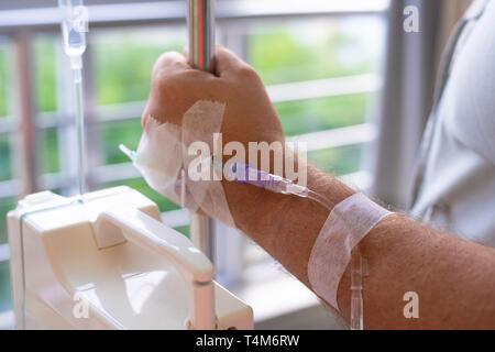 Close-up. Côté masculin avec un compte-gouttes pendant la chimiothérapie dans un hôpital. La main avec un compte-gouttes. La santé est un sujet de la santé et de la guérison Banque D'Images