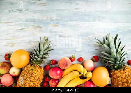 Variété de fruits sur la vieille table en bois. Ananas, banane, pomme, berry, d'agrumes et de pêche. L'alimentation saine manger propre sélection. Vue d'en haut. Copy space Banque D'Images