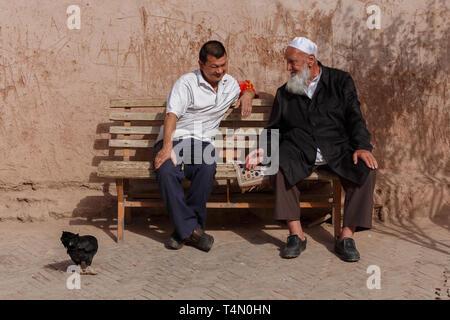 Deux hommes Ouïghours ayant une conversation sur un banc. Détail remarquable: le poulet sur le côté gauche des deux messieurs. Kashgar, la Province du Xinjiang, en Chine. Banque D'Images