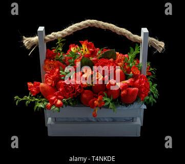 Cadeau fait main unique composé d'une fraise mûre et de roses rouges emballés dans une boîte en bois. Vue latérale sur fond noir Banque D'Images
