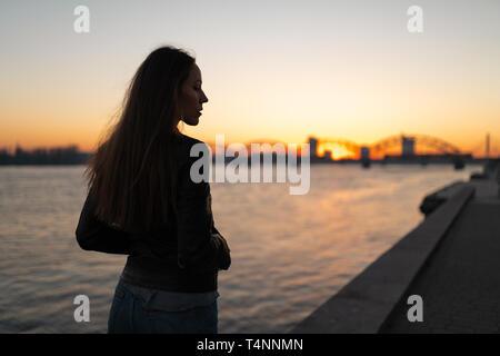 Jeune femme bénéficiant d'un coucher du soleil à pied le long de la Daugava avec vue sur ciel bleu clair