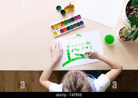 La jeune fille peint une maison verte . Concept de l'écologie Protection de l'environnement. Affectation d'école la créativité des enfants. Banque D'Images