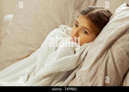 Pour attraper un rhume. Cute peu à peu malade fille brune avec une température élevée enveloppé dans une couverture blanche couchée dans un lit. Banque D'Images