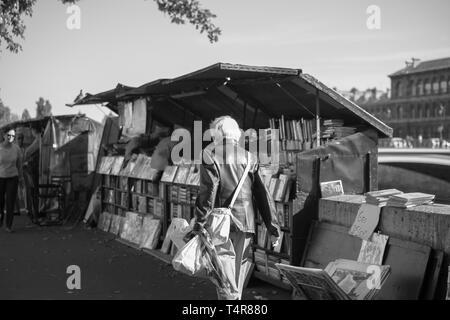 Femme à la navigation sur le trottoir du marché du livre, Quai de Seine, Paris, France Banque D'Images