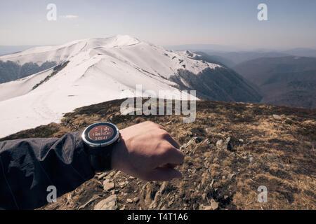 Contrôle des progrès sur smart Runner watch. Runner mâle l'entraînement à l'exercice et le saut à l'extérieur dans une vue magnifique sur la montagne nature paysage Banque D'Images