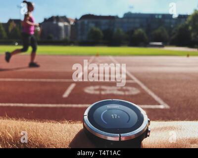 Contrôle sur les progrès formateur smart watch. Coureuse runnng sur le sport arena Banque D'Images