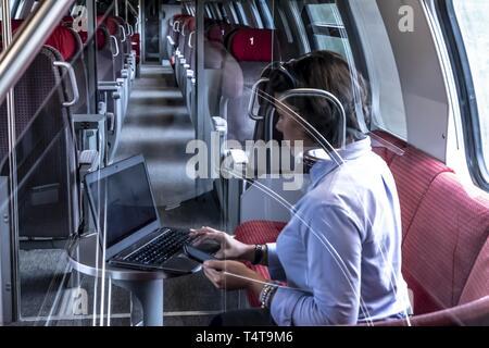 Business woman en train de première classe, le travail avec ordinateur portable et téléphone mobile, Suisse