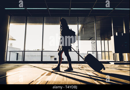 Silhouette de jeune fille qui marche à pied avec des bagages à l'aéroport au lever du soleil de la fenêtre de temps de voyage,voyage,concept de vie. Banque D'Images
