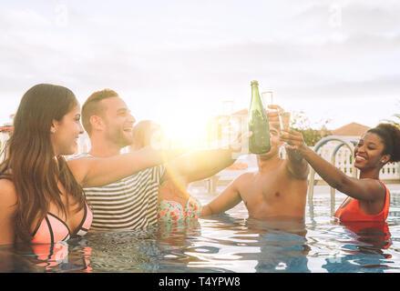 Heureux les amis faire une partie cheering with champagne - Les jeunes gens rire et s'amuser le grillage avec verres de vin pétillant Banque D'Images