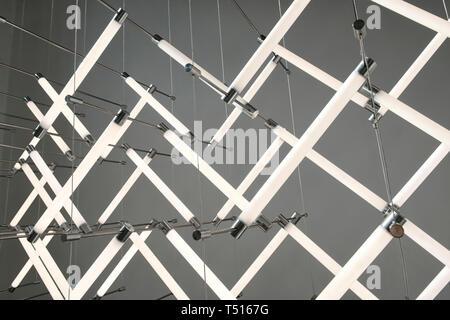 Gros plan sur la conception de l'éclairage au néon modernes avec lampes stick blanc accroché sur une fine couche de métal. Vue en gros plan contre mur gris Banque D'Images