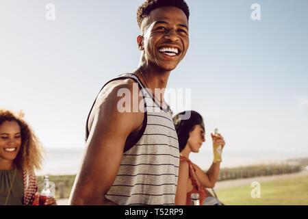 Heureux jeune homme sortir avec ses amis un jour d'été. Smiling man and woman friends la marche à l'extérieur avec des bières. Banque D'Images