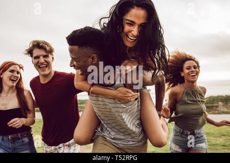 Smiling group of friends enjoying sur Fin de semaine. Multi-ethnic hommes et femmes s'amuser en plein air. Man carrying woman dans son dos et en cours d'exécution avec des amis