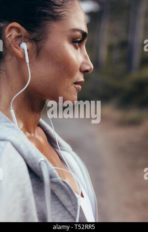 Close up d'une coureuse avec écouteurs standing outdoors. Femme d'écouter de la musique pendant l'entraînement à l'extérieur en matinée.
