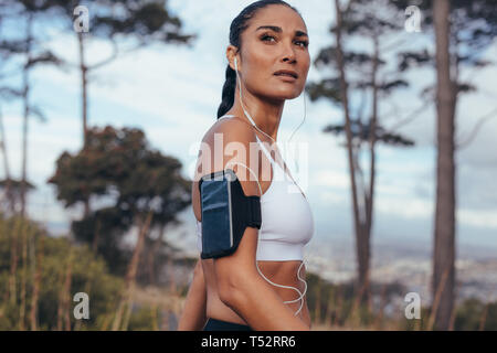 Femme sportive avec brassard smartphone outdoor randonnée en matinée. Femme de remise en forme sur les exercices du matin.