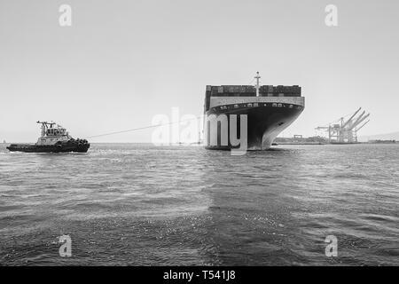 Photo en noir et blanc du navire porte-conteneurs, CMA CGM CENTAURUS, tourné de 180 degrés par un remorqueur JOHN QUIGG, avant d'arriver à Long Beach, USA. Banque D'Images