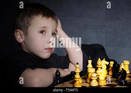 Un enfant d'âge préscolaire joue aux échecs. Le petit garçon est la réflexion sur le déménagement. Le cours du cheval.