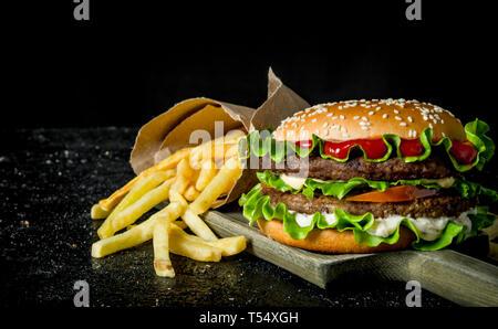 Hamburger et des frites sur la planche à découper. Noir sur fond rustique Banque D'Images