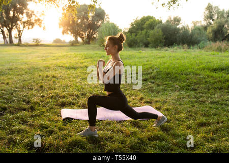Young woman practicing yoga in park