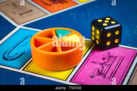 Londres, Royaume-Uni - 07 Avril 2019: classique jeu de Trivial Pursuit avec die noir et pièces en plastique de couleur de différentes couleurs
