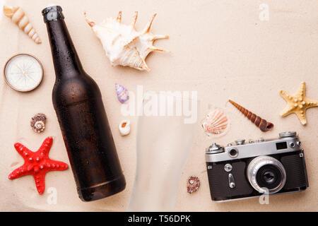 Bouteille de bière en verre et sur une plage de sable. Banque D'Images