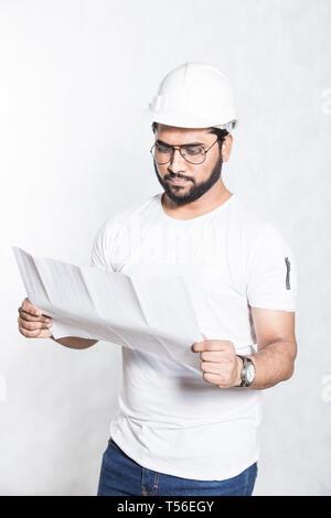 Un jeune travailleur de la construction avec des lunettes et un casque de protection blanche porte sur le dessin d'un bâtiment.