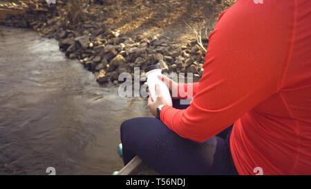 Caucasian woman sportsman dans des chaussures de sport casque repose sur le pont traverse la rivière. Cycliste dans des vêtements de sport à une fiole d'une matière plastique Banque D'Images