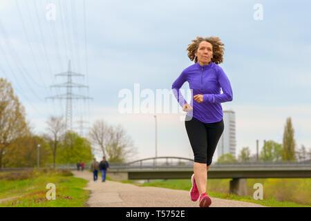 Femme d'âge moyen actif en hiver jogging le long d'une rivière urbaine dans un angle bas sur toute la longueur à l'approche de l'appareil photo avec copie espace Banque D'Images