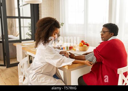 Jeune infirmière bouclés en veste blanche contrôle de la pression pour femme Banque D'Images