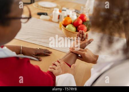 Femme dans les verres en mettant sa main sur la table pour l'infirmière pour mesurer le pouls Banque D'Images