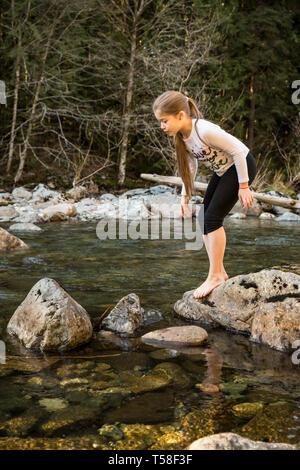 Olallie State Park, près de North Bend, Oregon, USA. Neuf ans, fille d'hésiter et de réfléchir à deux fois avant de sauter à la prochaine rock dans le nord f Banque D'Images