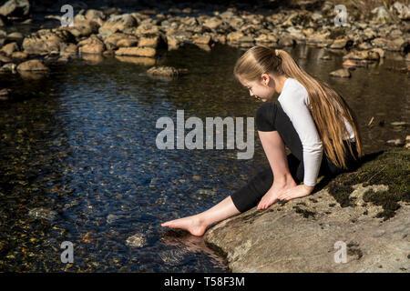 Olallie State Park, près de North Bend, Oregon, USA. Neuf ans, fille d'essais avec précaution la froideur de l'embranchement nord de la rivière Snoqualmie, avec Banque D'Images