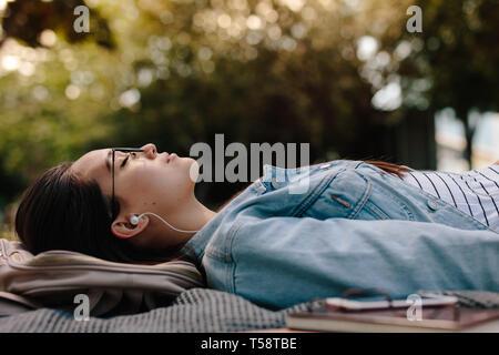 Gros plan d'une femme dormant dans un parc à l'écoute de musique. Niveau du sol tourné d'une jeune femme étendue sur le sol portant des lunettes avec des livres à côté d'elle
