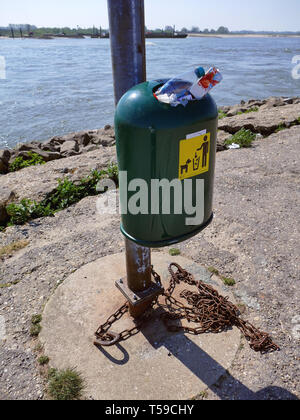 OCHTEN, Pays-Bas - 21 avril 2019: poubelle pleine sur un lieu public près d'une rivière. Une chaîne de métal sur le sol autour du poteau auquel le bin Banque D'Images