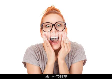 Closeup portrait de femme perplexe avec ginger hair bun lunettes en gardant les mains sur les joues, à la grande surprise de choc avec stupéfaction, en huis clos Banque D'Images