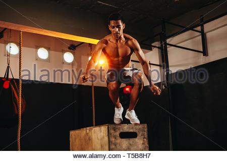 Jeune homme fit faire un saut de l'exercice. L'homme faisant un sport fort squat dans la salle de sport Banque D'Images