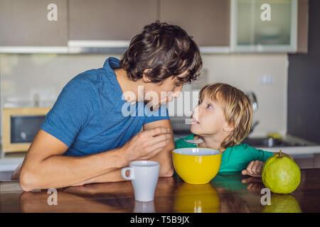Père et fils sont en conversation et sourire tout en ayant un petit-déjeuner dans la cuisine Banque D'Images
