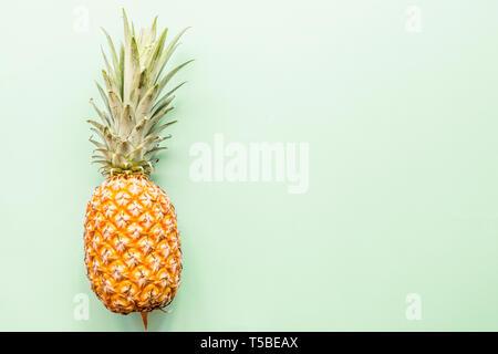 L'ananas frais allongé sur fond vert. Vue d'en haut. Concept de mise à plat. Place pour le texte Banque D'Images