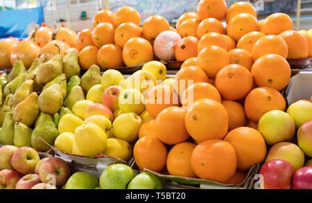 Arrière-plan lumineux de fruits frais. Les oranges, les pommes, les poires se trouvent dans les bacs dans le marché et attirer l'attention. Banque D'Images