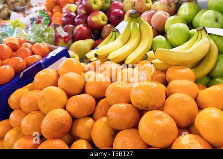 Arrière-plan lumineux de fruits. les mandarines, bananes, pommes résident dans les bacs dans le marché et attirer l'attention. Banque D'Images