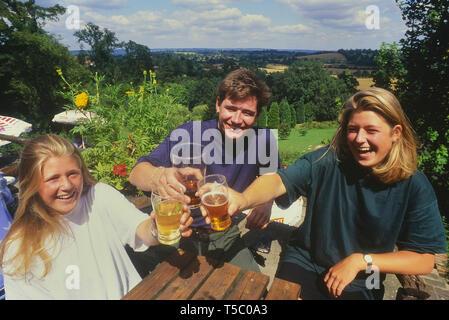 L'éducation de leurs jeunes buveurs de boissons pour la caméra à la pub Spotted Dog jardin. Penshurst. Kent. L'Angleterre. UK Banque D'Images