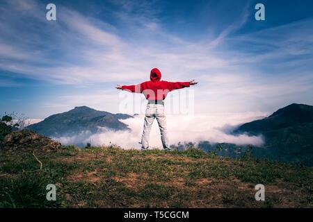 Femme heureux séjour à bras ouverts sur le sommet de la montagne falaise sous ciel lumière profitant du succès, de la liberté et de l'avenir brillant. effet de la flig Banque D'Images