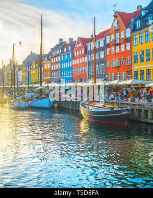 Voir Nyhavn avec des bateaux par remblai au coucher du soleil, les gens marcher et s'asseoir dans les restaurants, Copenhague, Danemark