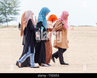 Cinq femmes musulmanes portant le hijab la marche sur la plage dans le parti conservateur de l'État de Kelantan en Malaisie.