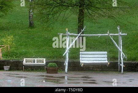 Balançoires blanc dans le jardin après la pluie d'été sont enveloppées dans des vapeurs de brouillard dans le contexte de l'herbe verte juteuse et de flaques sur le trottoir t Banque D'Images