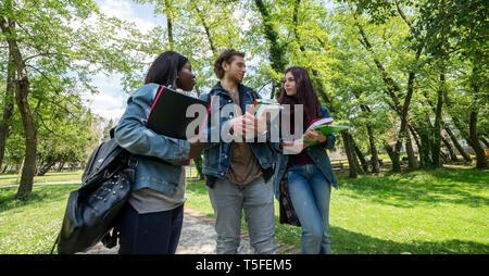 Groupe de multi-ethnic girls student walking dans le parc en attente de la leçon à l'université Banque D'Images