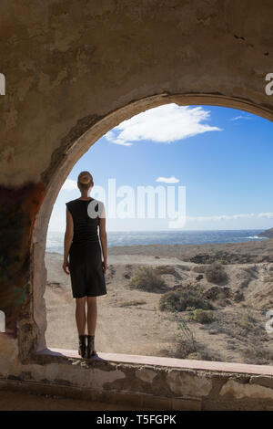 Espagne, Ténérife, Abades, Sanatorio de Abona, woman standing at fenêtre cintrée dans Ghost Town building Banque D'Images