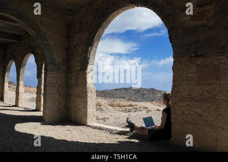 Espagne, Ténérife, Abades, Sanatorio de Abona, woman sitting in ghost town building using laptop Banque D'Images