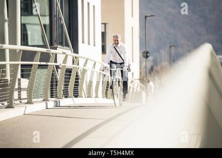Smiling mature woman riding bicycle sur un pont de la ville